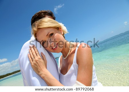 Bride and groom embracing by the sea - stock photo