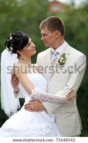 Bride and groom embracing in the park - stock photo