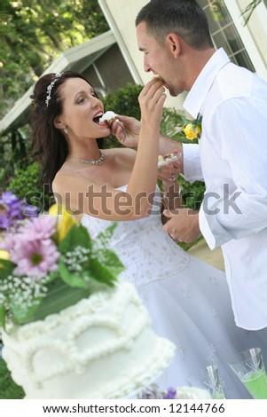 bride and groom feeding cake - stock photo
