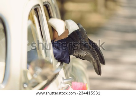 bride and groom feet in car window - stock photo