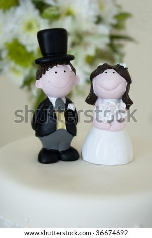 Bride and groom figurines on top of a wedding cake - stock photo