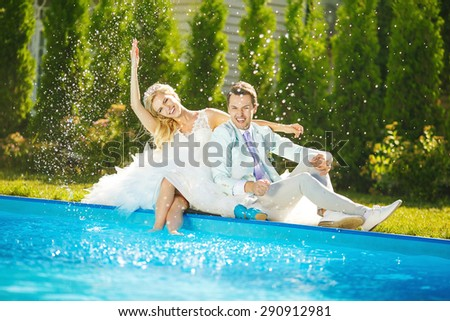 Bride and groom fooling around in the water near the swimming pool