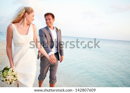 Bride And Groom Getting Married In Beach Ceremony - stock photo