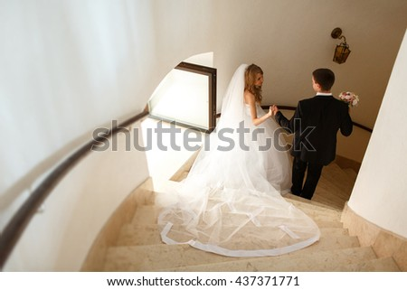 Bride and groom go downstairs through a fortress entrance
