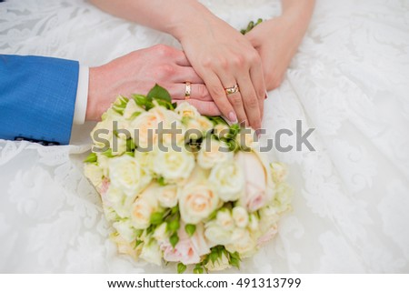 Bride and groom hands on the wedding flowers