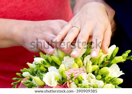 Bride and groom hands with engagement rings and bridal bouquet