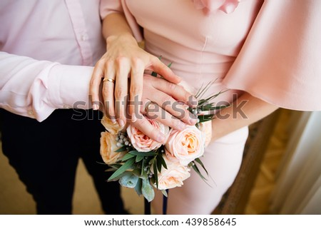 Bride and groom hands with engagement rings and wedding bouquet - stock photo