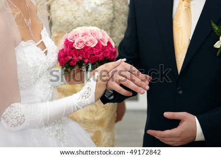 Bride And Groom Hands with Wedding Rings and Flowers Bouquet - stock photo
