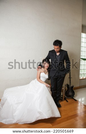 Bride and groom happy sitting on the woodden bench with back guitar on white background.