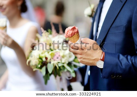 Bride and groom having an ice cream outdoors on a wedding day - stock photo