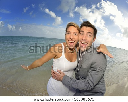 Bride and groom having fun at the beach - stock photo