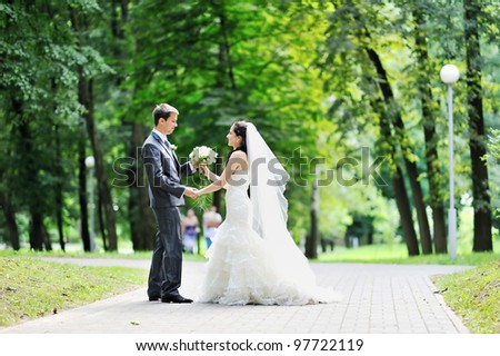 Bride and groom having fun in a park - stock photo