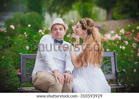 Bride and groom having fun in park - stock photo