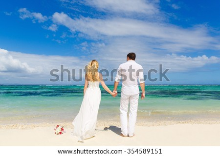 Bride and Groom having fun on the tropical beach with his back to the viewer. Wedding and honeymoon concept. - stock photo