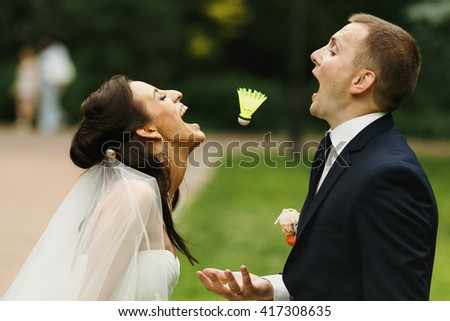 Bride and groom having fun trying to catch with their mouthes a shuttlecock