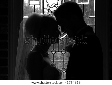 bride and groom head to head at the window - black and white - stock photo