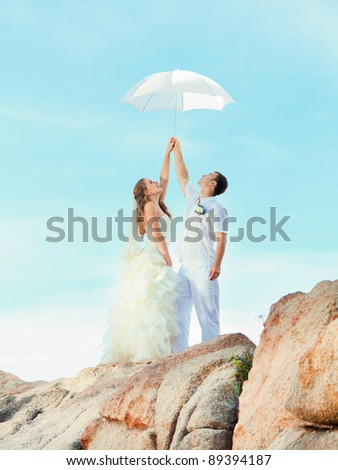 Bride and groom holding an umbrella on a rock.