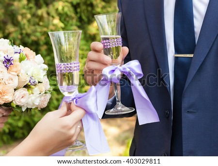 bride and groom holding beautifully decorated wedding glasses with champaign - stock photo