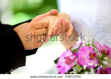 Bride and groom holding bouquet - stock photo