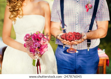 bride and groom holding bouquet and raspberry - stock photo