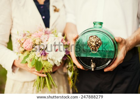 bride and groom holding bouquet and wine - stock photo