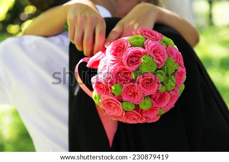 Bride and groom holding bridal bouquet close up - stock photo