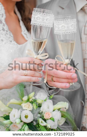 bride and groom holding flutes with champagne - stock photo