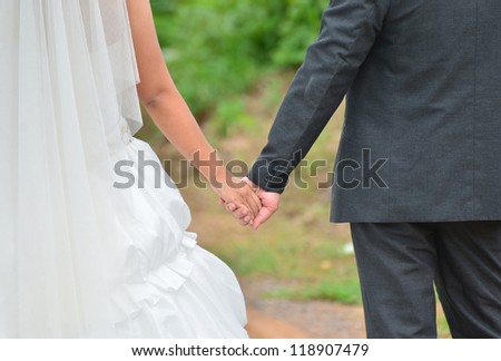 Bride and groom holding hand each other