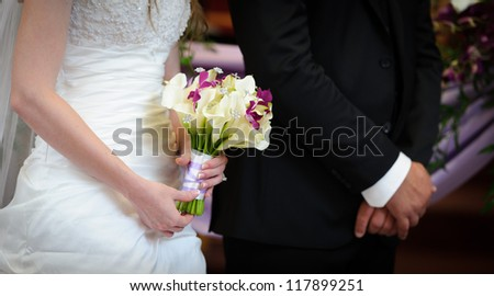 Bride and groom holding hands - stock photo