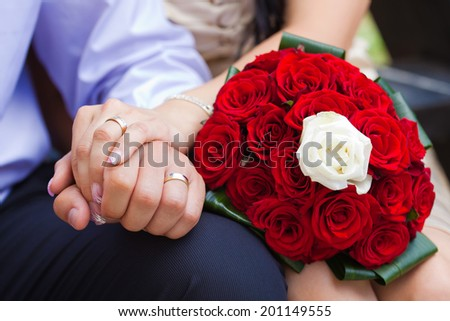 Bride and groom holding hands and showing the engagement rings  - stock photo