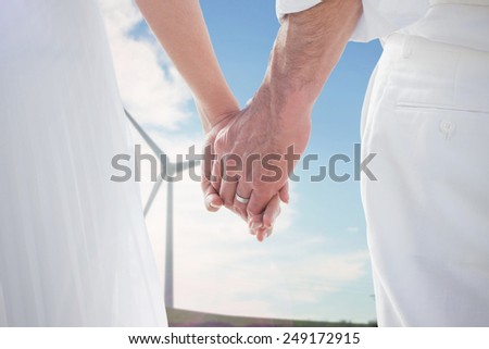 Bride and groom holding hands close up against windmill spinning over a green field - stock photo