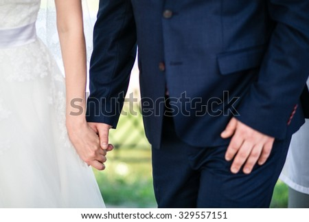 Bride and groom holding hands during the wedding ceremony, closeup