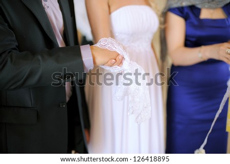 bride and groom holding hands in scarf at church ceremony - stock photo