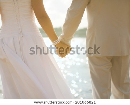 Bride and groom holding hands in sunny summer day on sea - stock photo