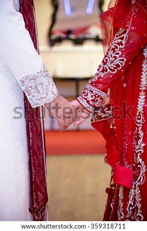 bride and groom holding hands indian - stock photo