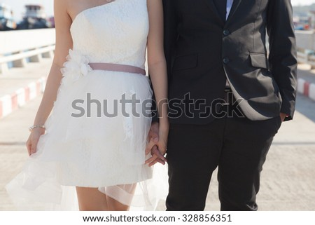 Bride and groom holding hands Love and relationships of couples. - stock photo