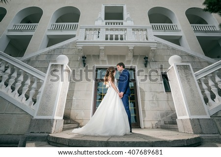 Bride and groom holding hands standing in the background of the building with beautiful architecture. Happy young wedding couple.