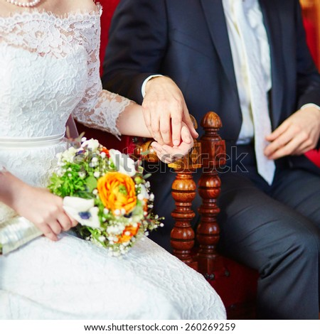 Bride and groom holding hands tenderly during the wedding ceremony - stock photo