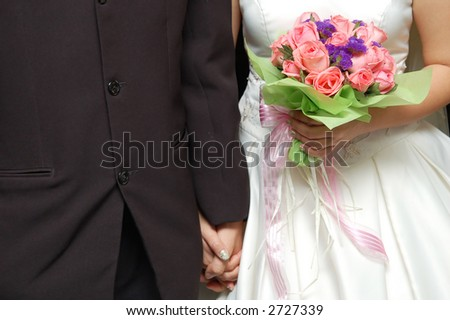 bride and groom holding hands with bouquet of pink roses - stock photo
