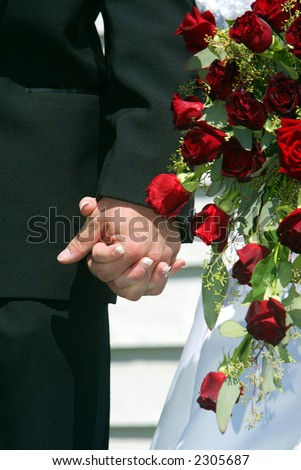 Bride and Groom Holding Hands with Red Rodes - stock photo