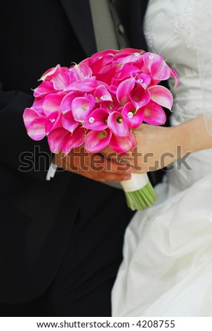 Bride and groom holding hands with wedding bouquet.