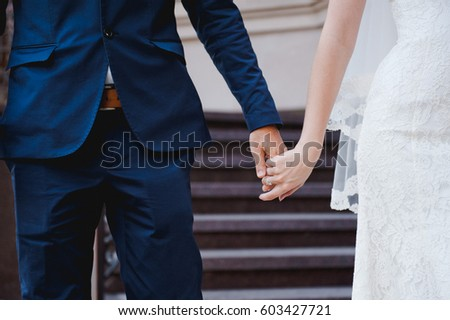 Bride and groom holding hands with wedding ring. Bride and groom.
