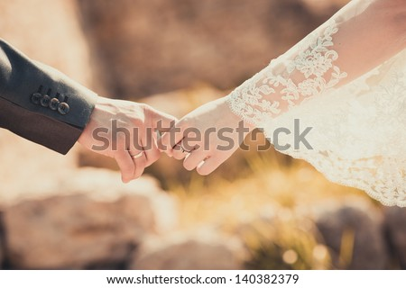 Bride and groom holding his hands - stock photo