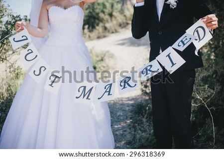 "Bride and groom holding ""Just married"" sign. Wedding day - stock photo"