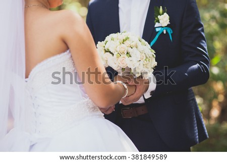 Bride and groom holding the flowers in hands