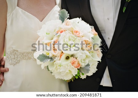 Bride and groom holding wedding bouquet together - stock photo