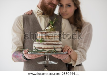 Bride and groom holding wedding cake together - stock photo
