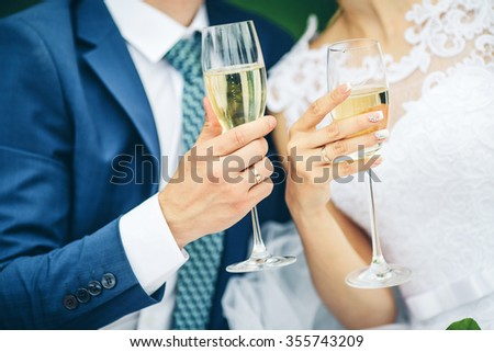 Bride and groom holding wedding champagne glasses - stock photo
