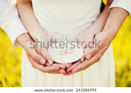 bride and groom holding wedding rings - stock photo
