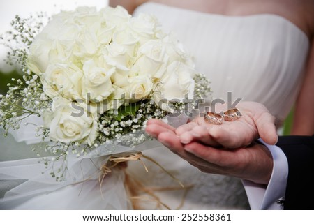 Bride and groom holding wedding rings and a bouquet of flowers - stock photo